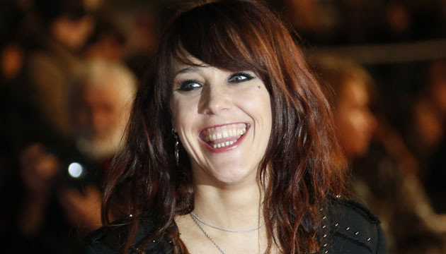 French singer Zaz smiles while arriving at the Palais des Festivals to attend the 16th Annual NRJ Music Awards on December 13, 2014 in Cannes, southeastern France.  AFP PHOTO / VALERY HACHE